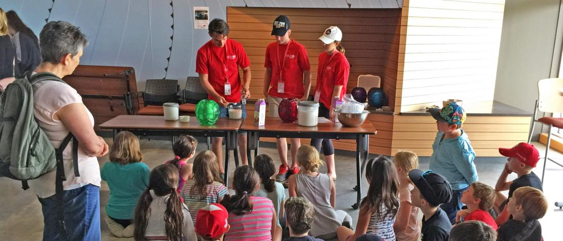 Three volunteers do a demonstration for a large group of children on a field trip.