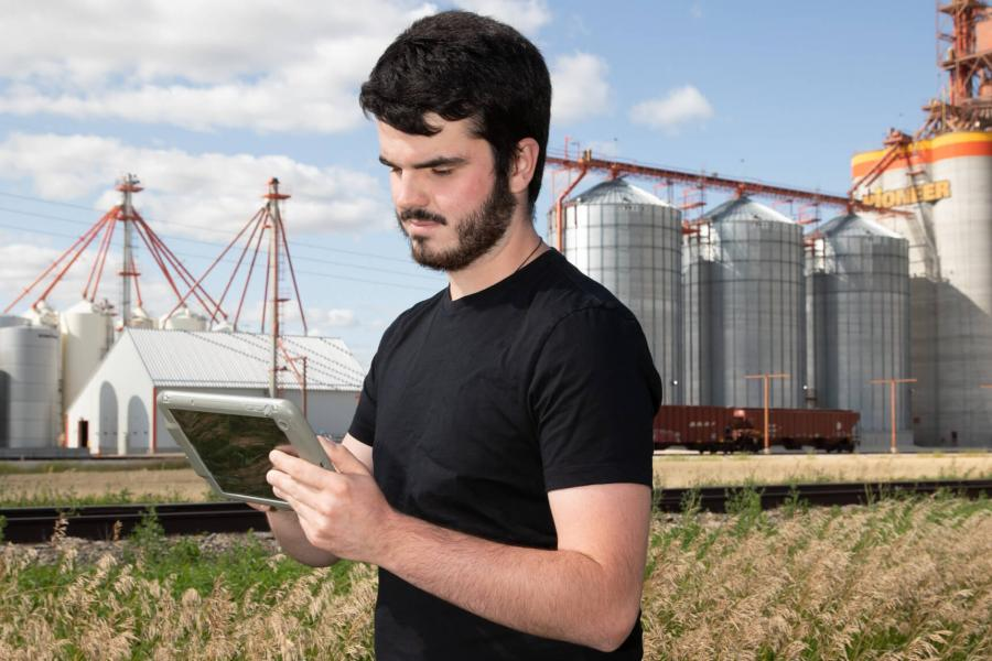 A student uses a piece of equipment while standing in a field with a large grain elevator in the background.