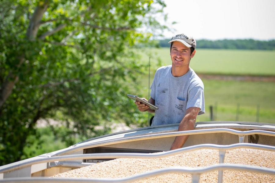 A student stands at the top of a grain truck taking samples.