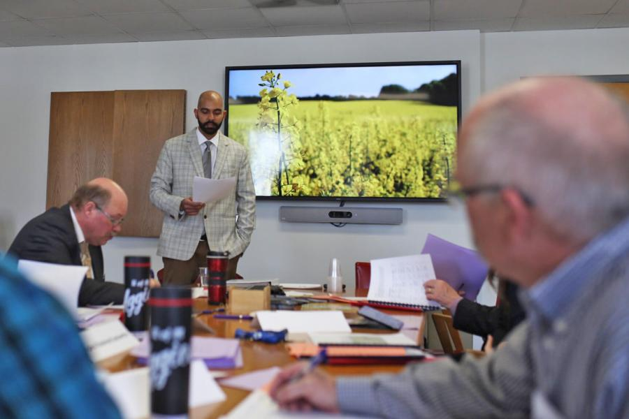 People gather around a boardroom table while someone makes a presentation, a television in the background shows a field of canola.