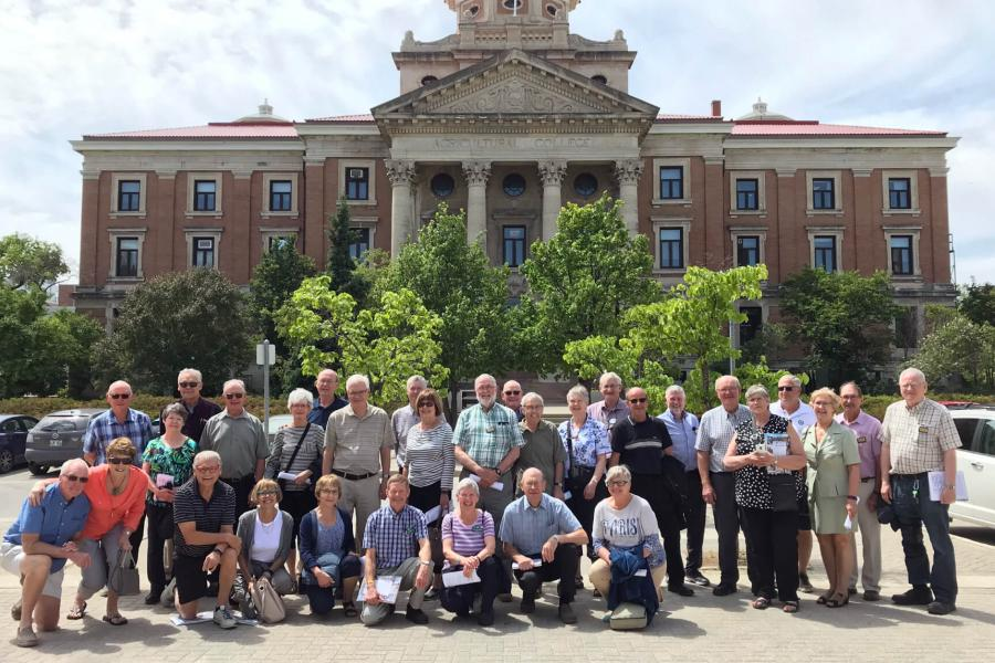 A large group of alumni from the Faculty of Agricultural and Food Sciences stand together in front of the Administration building on the Fort Garry campus.