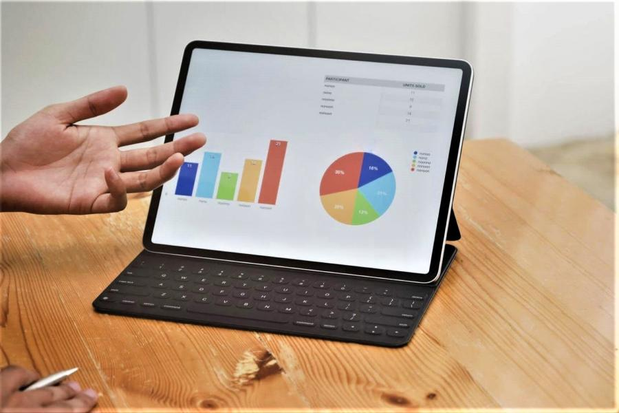 Laptop computer displaying graphs with a hand gesturing in explanation.