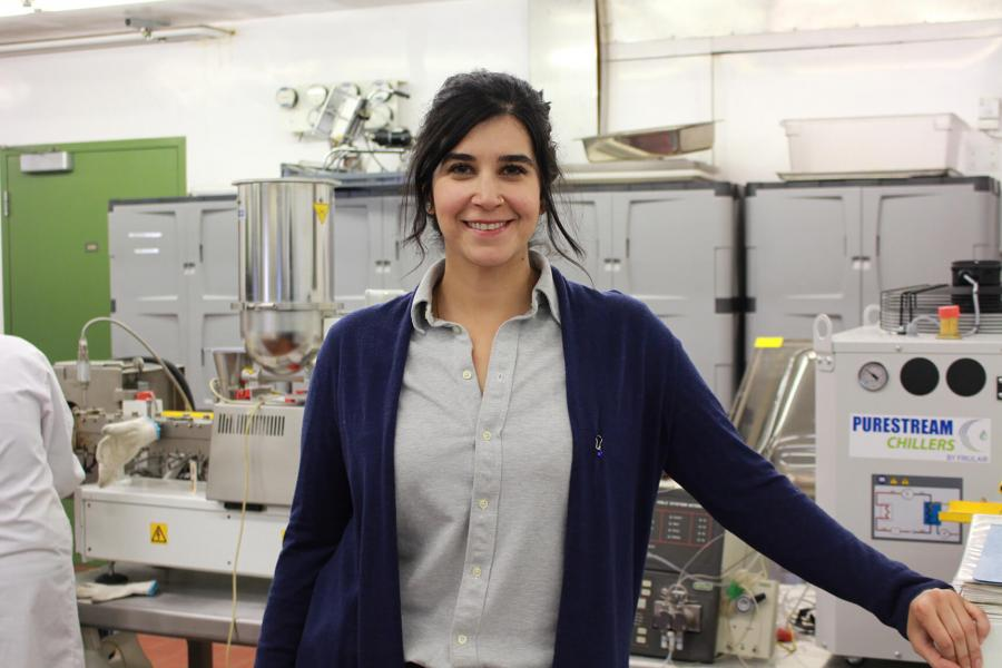 Filiz Koksel stands in front of food processing equipment.