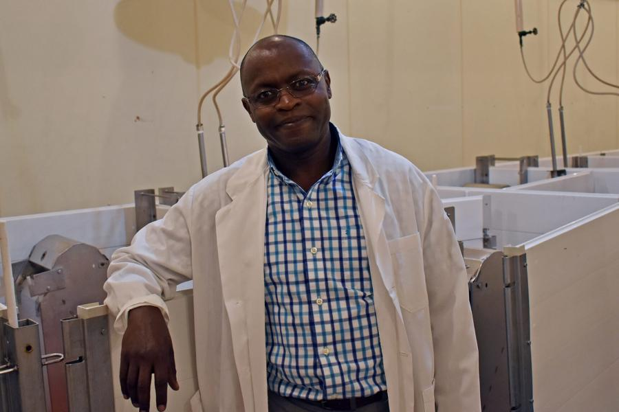 Martin Nyachoti standing in front of animal pens.