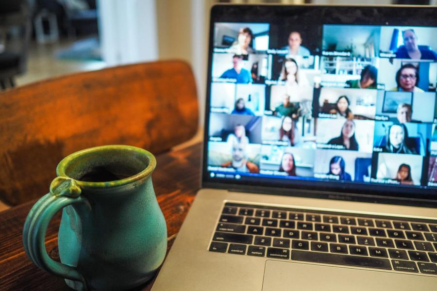 Cup of coffee beside laptop with video conference