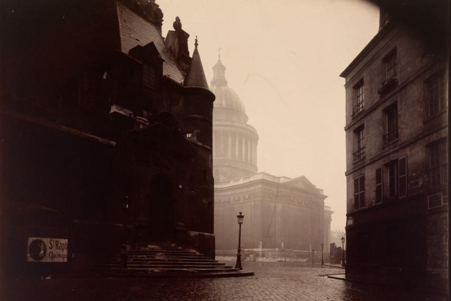 An old photograph of a street and buildings.