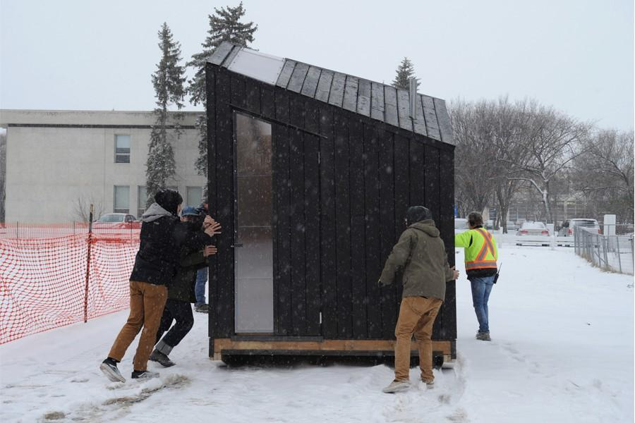 students moving ice shack in winter