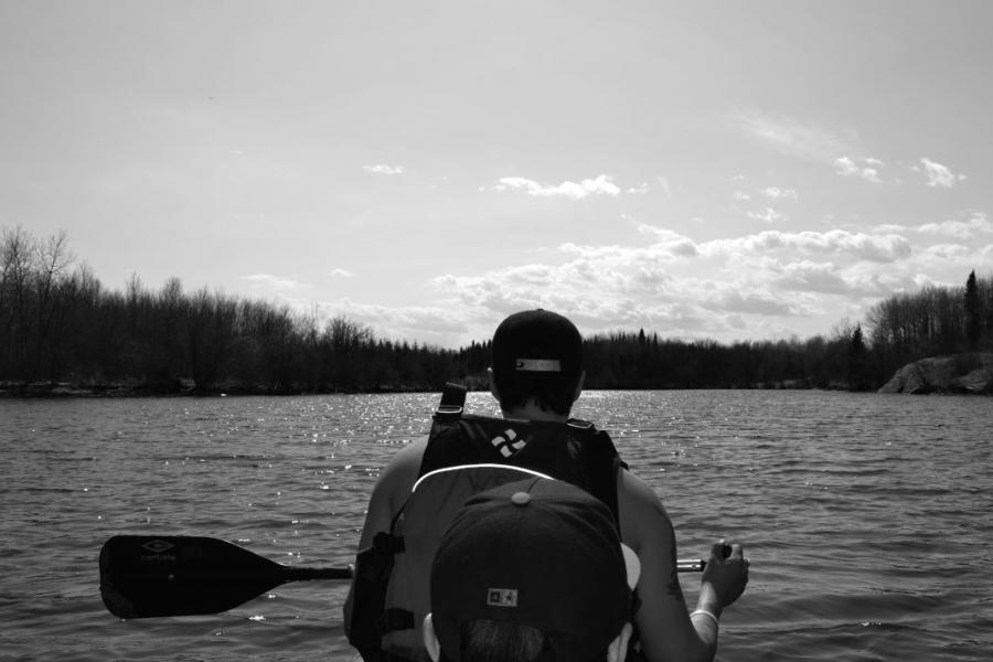 guy from behind paddling on a canoe in black and white
