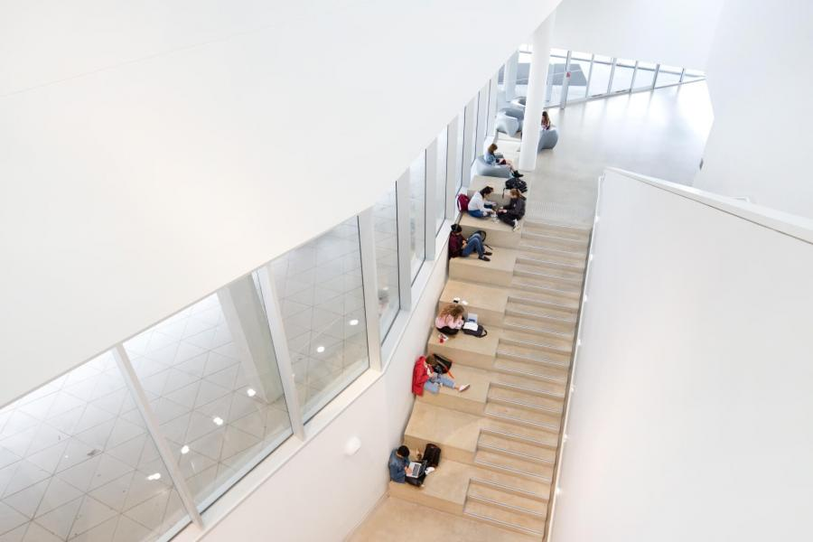 An upper level view of a staircase with students studying in the ArtLab building.