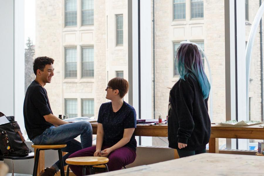 Three School of Art students sit at a narrow table in front of a window.