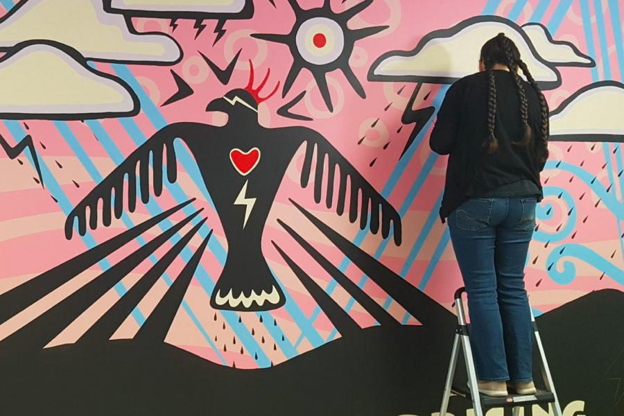 An indigenous artist works on painting a large mural.