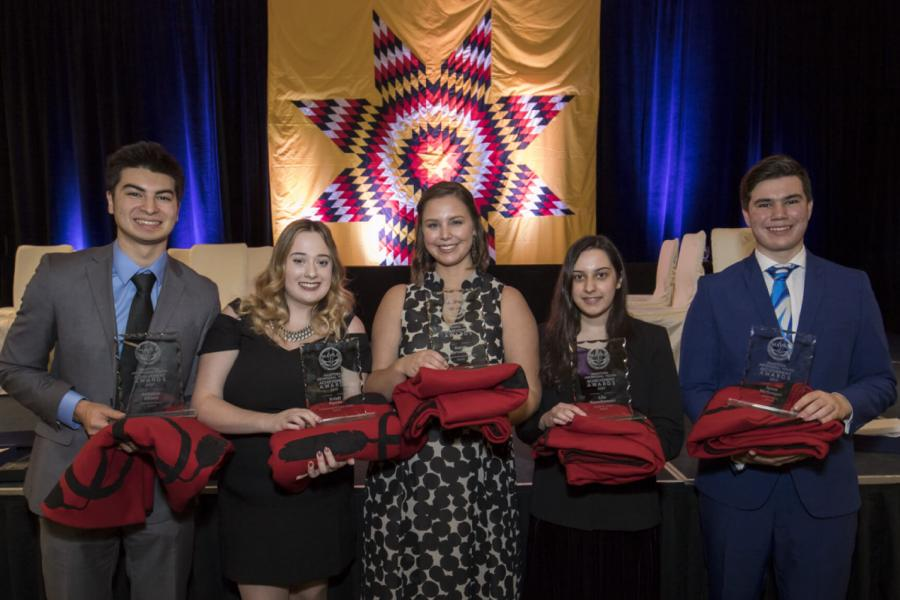 Five Indigenous Commerce Students stand side by side holding folded red blankets.