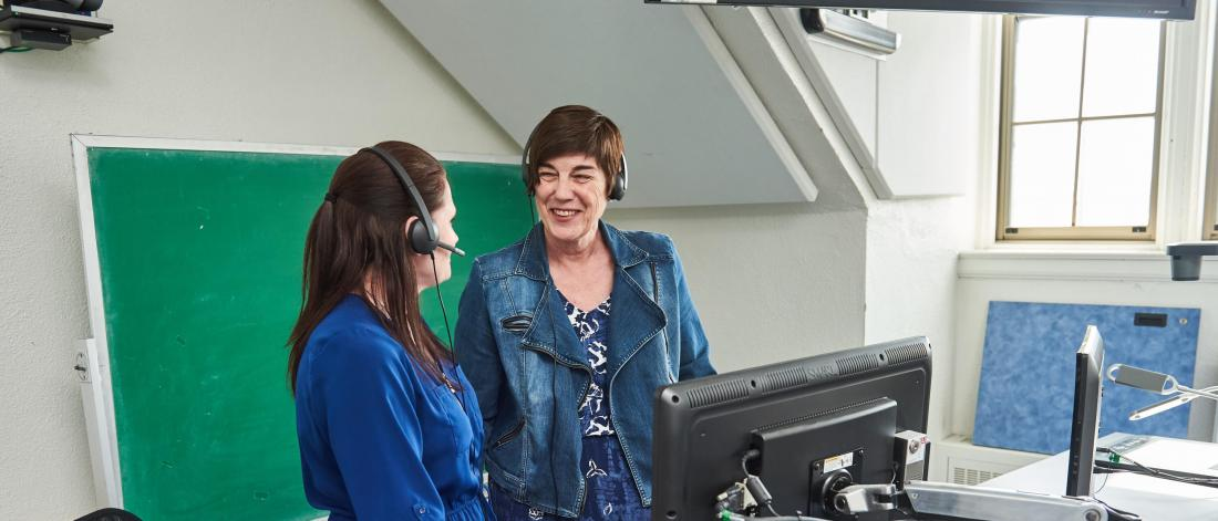 Two members of the Faculty of Social work work together in an office wearing headsets and standing in front of a computer work station.