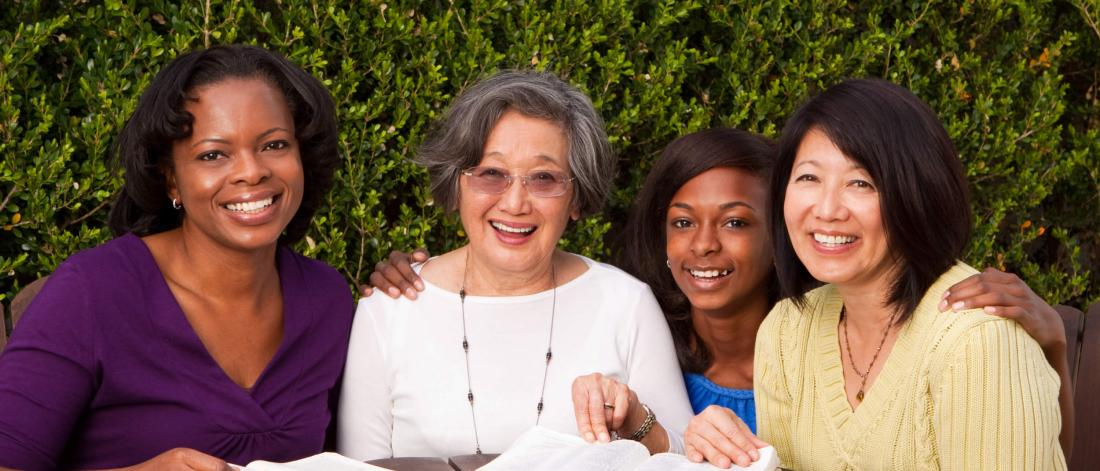 A diverse group of four women of varying ages are smiling and seated at a table.