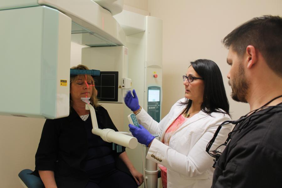 A facial imaging scan conducted on a patient as a dentists look on.