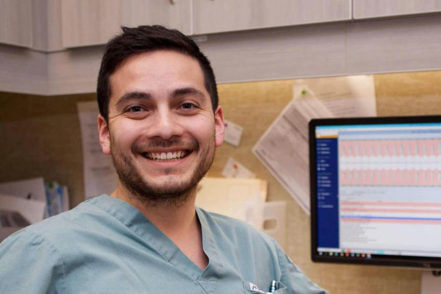 A college of dentistry student smiles as he sits at a desk with a computer work station.