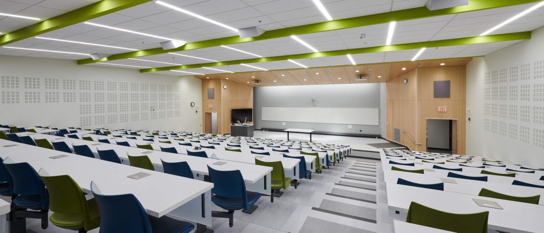 The brightly lit modern classroom space of room 290 from the back row looking towards the front of the room with rows of bright white tables and green and blue chairs.
