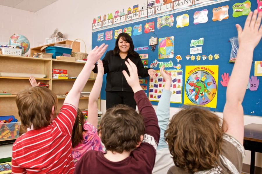 A smiling teacher stands in front of an elementary grade classroom full of excited students with raised hands.