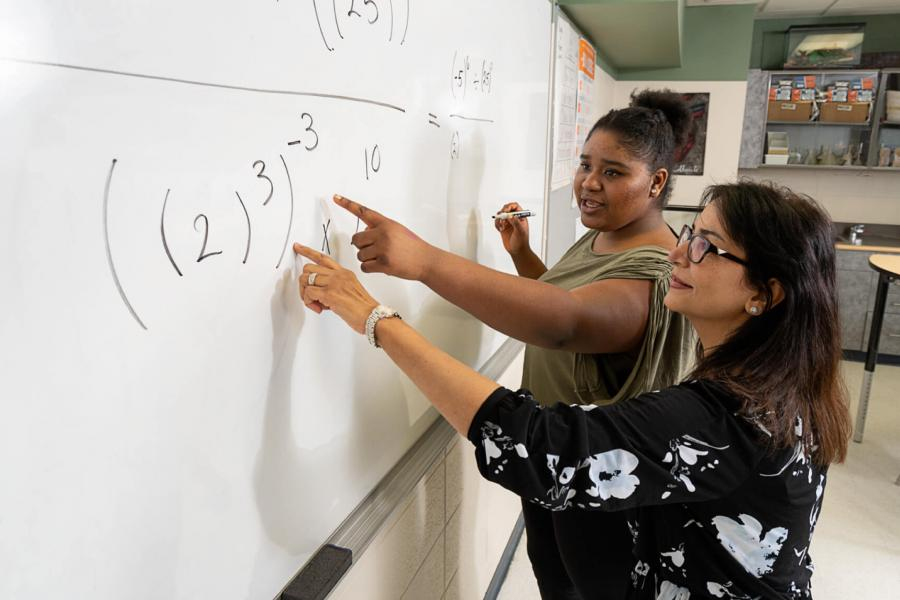 A teacher and student work together to solve a math problem on a whiteboard in a classroom.