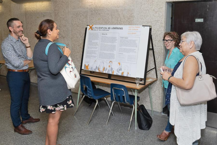 Assistant Prof. Joe Curnow, student Justin Fraser and two attendees talking at the 2019 Homecoming near a display for Politicization As Learning.