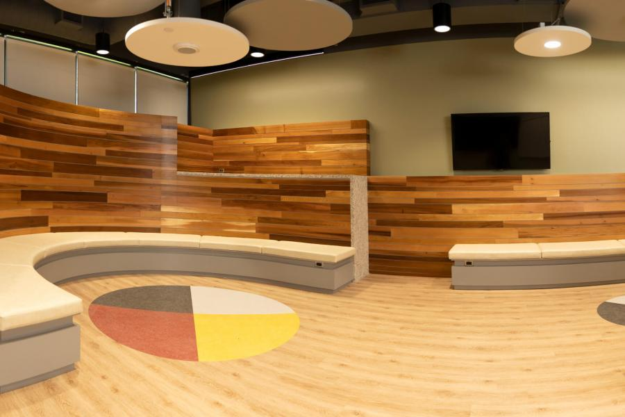 Interior view of the newly constructed Indigenous student community space with circular bench seating, and a medicine wheel built into the floor.