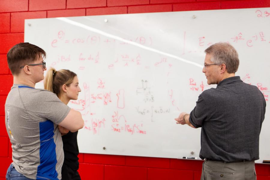 Two students stand at a white board while a professor speaks.