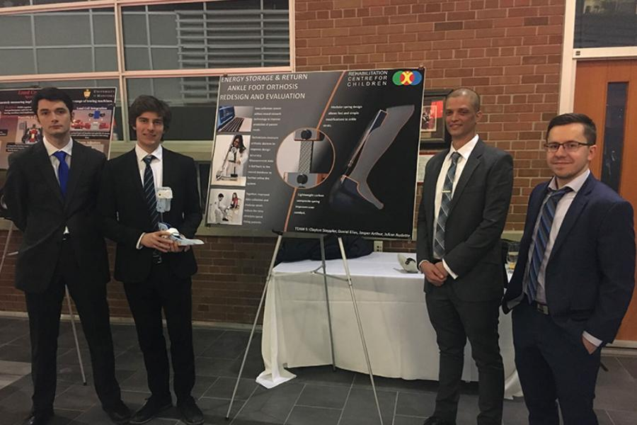 A team stands together beside their final capstone poster during the 2018 Mechanical Engineering Design Reception Evening.