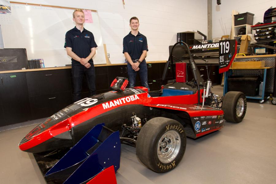Two mechanical engineering students stand behind a small racing car they have built.