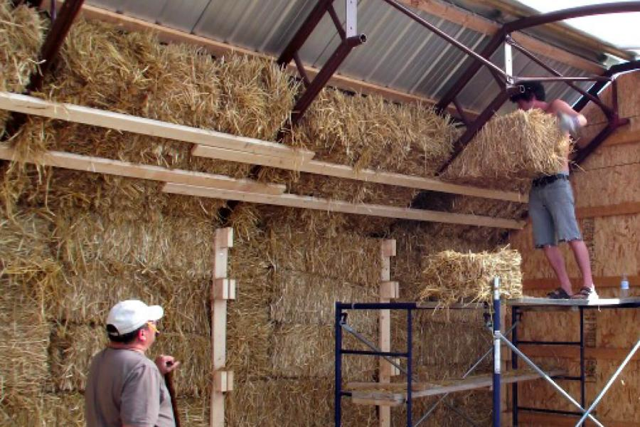 A man works on building an alternative village building by placing straw bales into a structure.