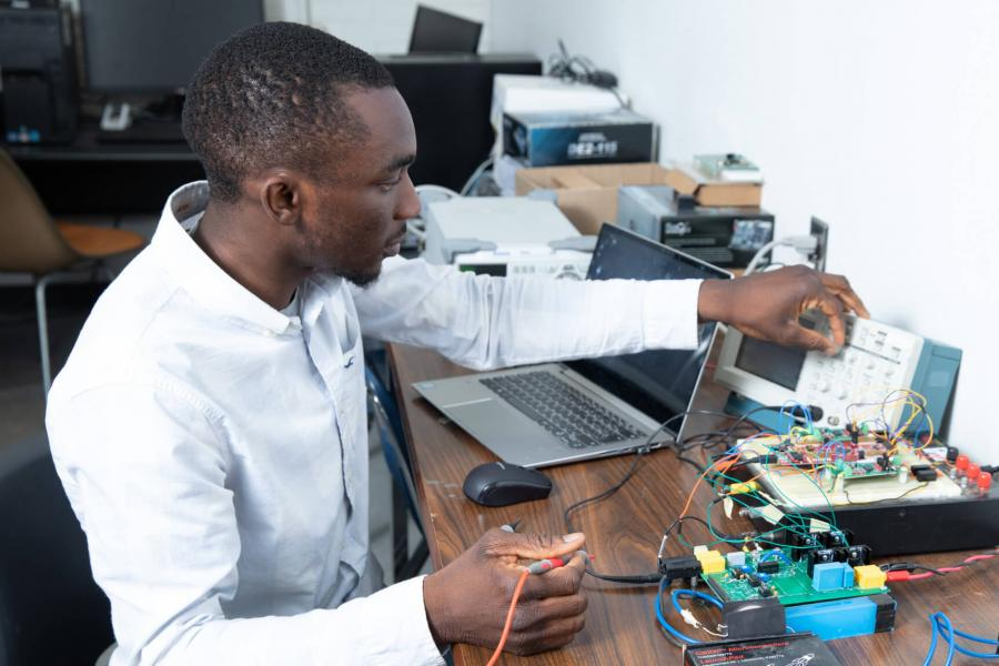 An engineering students sits at a desk while working with computer engineering equipment.