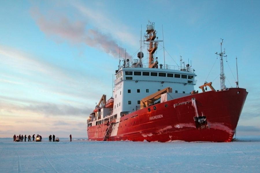 The Amundsen vessel stopped in frozen ice. Several crew members gather on the ice with three snowmobiles.