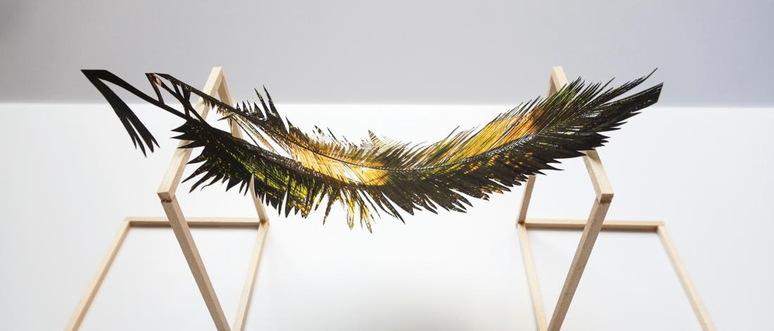 A metallic feather rests on a wooden stand.