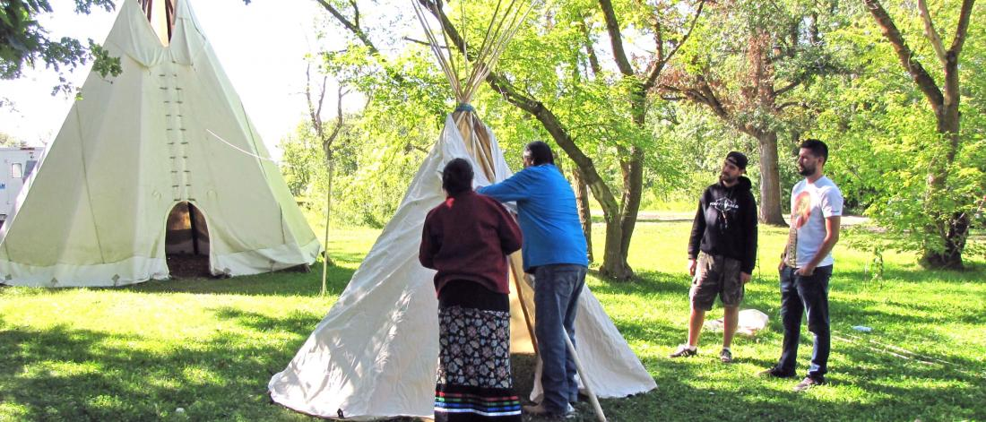 Two Indigenous elders work on making a teepee tent while two students observe.
