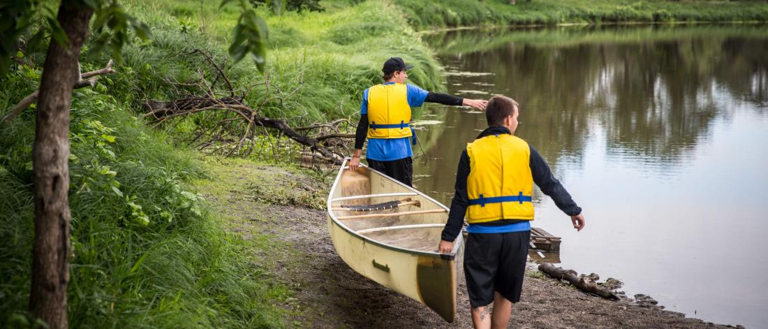 Two recreation management and community development students carry a canoe along the shore of a river.