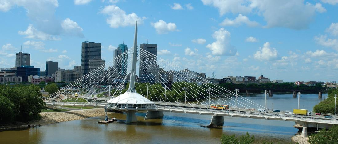 A scenic city scape of Winnipeg Manitoba prominently featuring the Provencher Bridge.