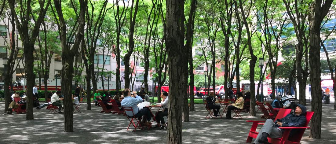 Several small groups of people seated on red outdoor furniture in an scenic outdoor space filled with trees.