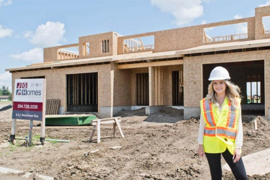 An architecture student stands in front of a partially built home for J and G homes where she is participating in a co-operative integrated work program.
