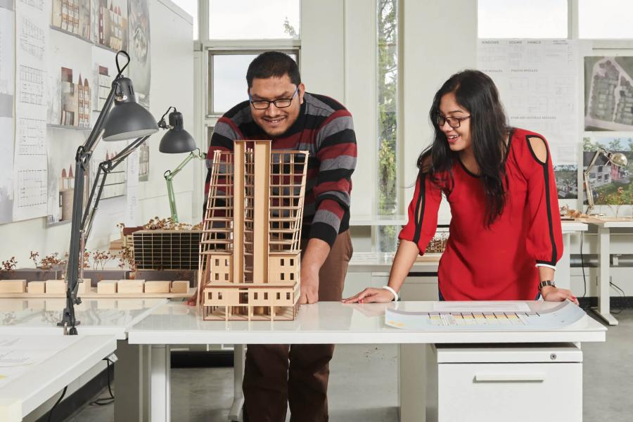 Two Faculty of Architecture students stand at a desk and look at a project they are working on together.