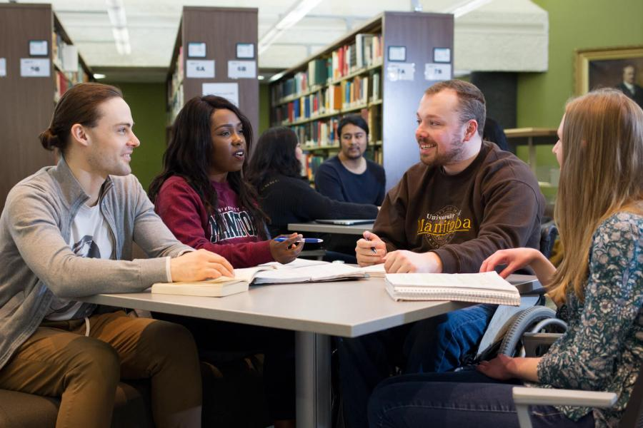 A diverse group of students sit at a table together in a library studying.