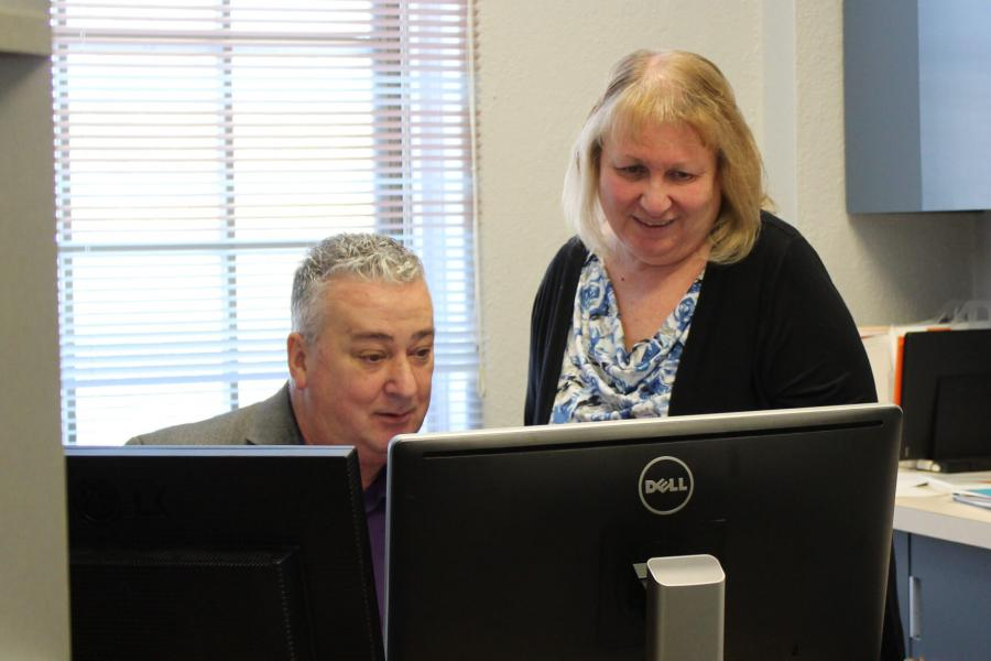 A social work student works at a computer with a supervisor.