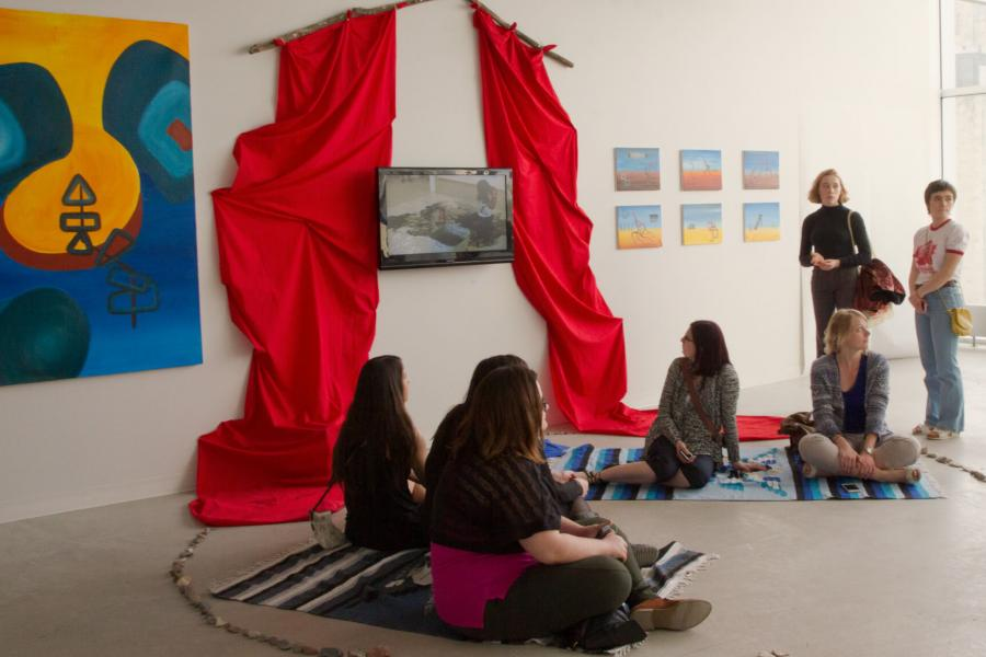 Kristin Flattery's exhibition space with a TV, hanging red fabric and various paintings.