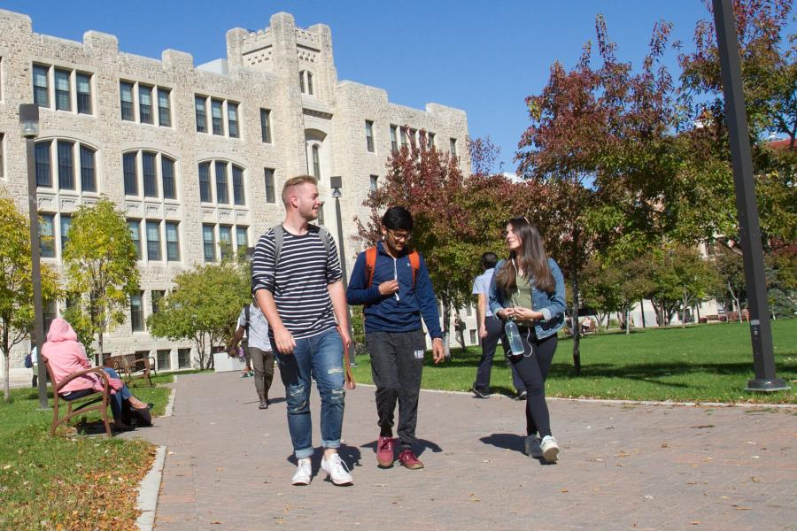 Three University of Manitoba students walk outdoors together at the Fort Garry campus.