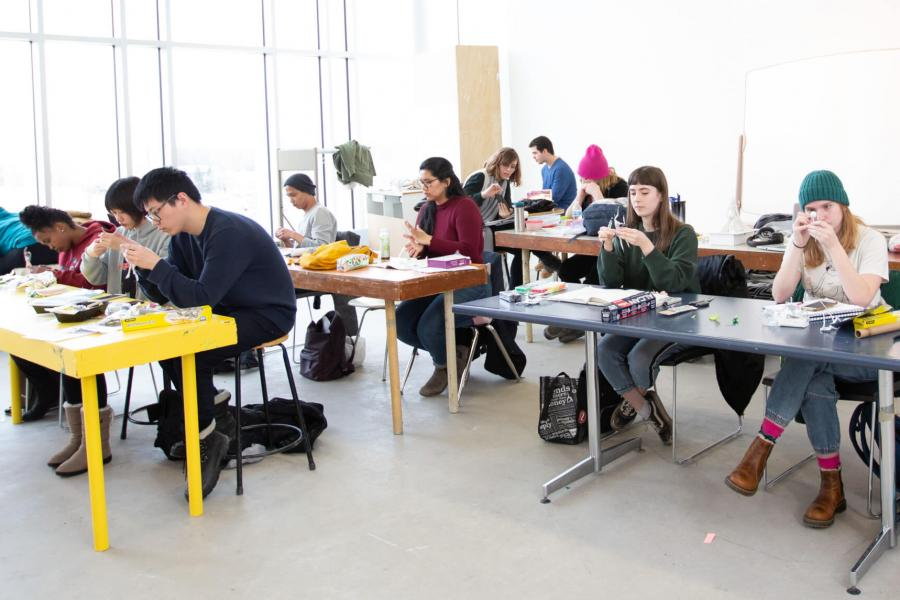 A class of first year school of art students work in a studio at long narrow tables.