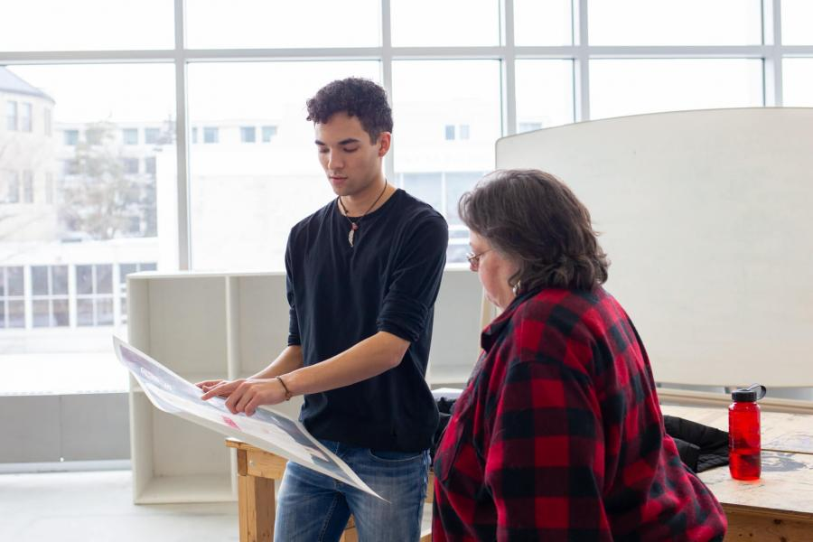 A student reviews his work with an instructor.