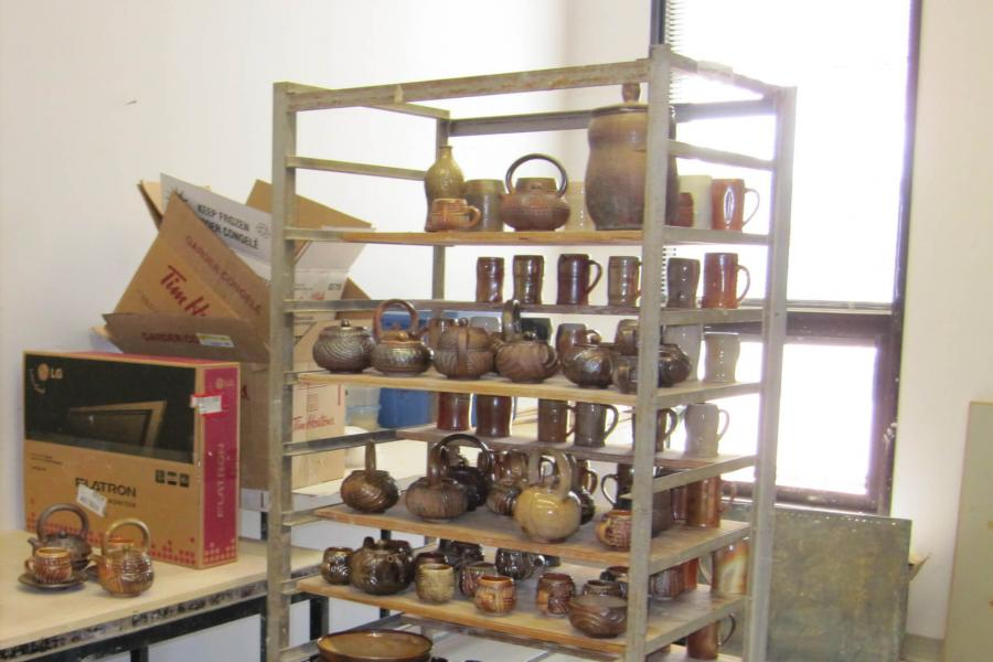 A shelving unit filled with finished ceramic pieces.