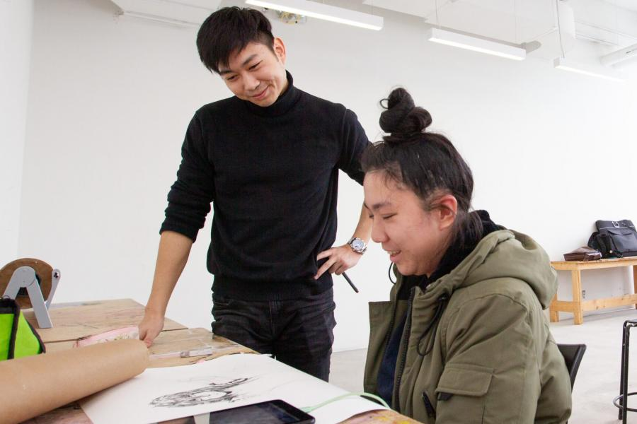 A smiling student looks at another students drawing work.