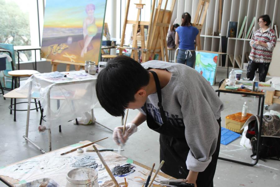Students paint in a brightly lit studio.