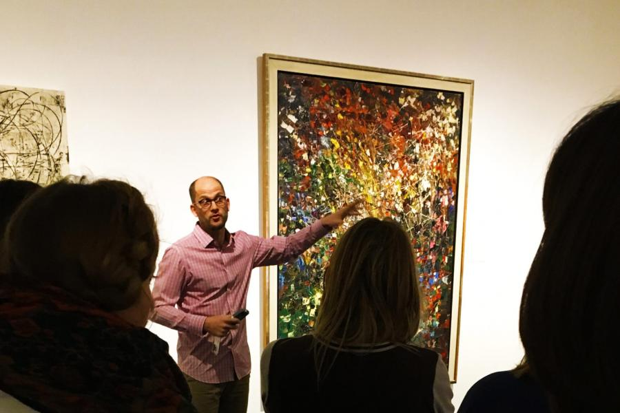 A crowd of people gather around as someone discusses a painting