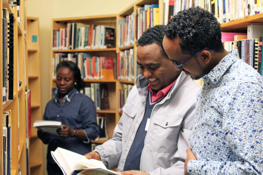 Three social work students look at books in the library.