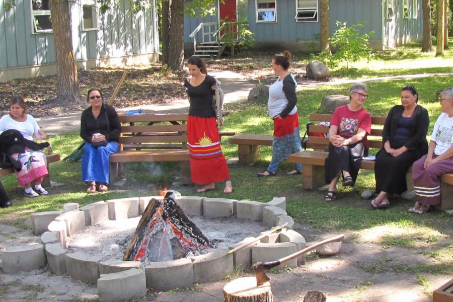 A group of social work student participants gather around a fire pit shaped like a turtle.